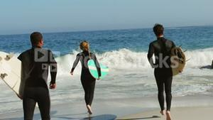 Friends in wet suits running into water
