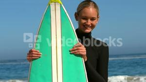 Woman in wet suit hiding behind surfboard