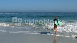 Woman running into water with surfboard
