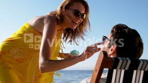 Woman applying sunscreen on the nose of a man