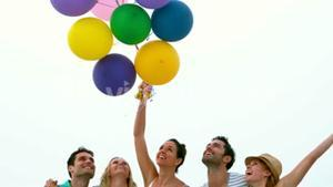 Smiling friends holding balloons