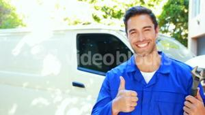 Repairman with tools and thumbs up