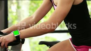 Fit woman using exercise bike and smart watch