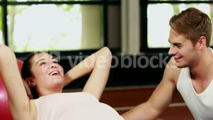 Trainer man helping woman doing her crunches