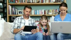 Cute family using technologies sitting on the couch