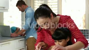 Mother teaching her daughter cutting vegetables