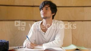 Handsome student taking notes