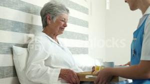 Nurse bringing food to senior woman