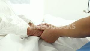 Nurse holding patient hands