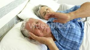 Senior man covering her ears while woman snoring