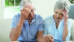 Worried senior couple looking at smartphone