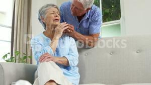 Senior woman crying and being comfort by husband