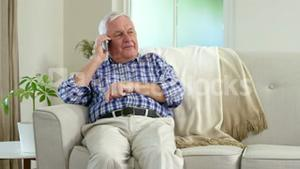Senior man on the phone on couch