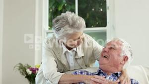 Senior couple embracing on couch