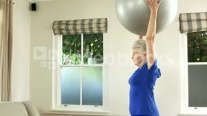 Senior woman lifting exercise ball