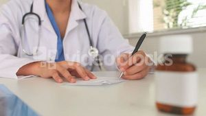 Young doctor writing a prescription