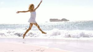 A woman is jumping with her white clothes
