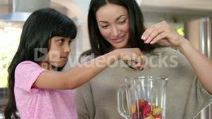 Mother and daughter cooking fruit in the kitchen