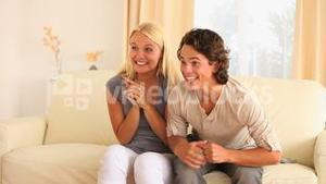 Excited couple sitting on a sofa