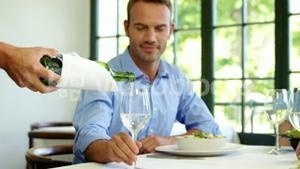 Businessman is being waited on a glass during lunch meeting