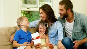 Family offering a gift to the son