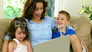 Mom and her children looking at computer on a couch