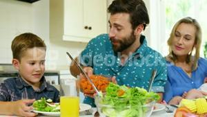 Dad serving carrot to his son