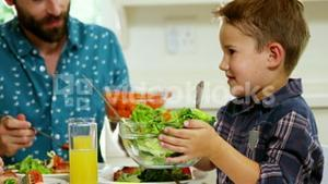 Boy giving the salad plate