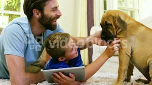 Father and son playing with a dog