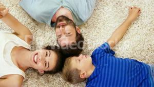 Happy family lying on carpet and pointing the camera