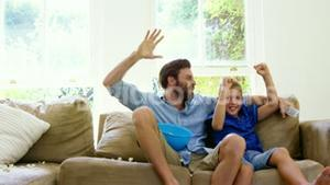 Happy father with son enjoying in front of the television