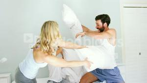 Happy family playing to pillows fight on bed
