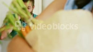 Man calling behind woman holding grocery bag