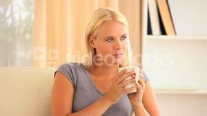 woman drinking coffe sitting on a sofa