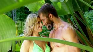 Cute couple looking each other in the middle of palm tree