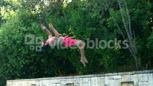 Handsome man doing a somersault on pool