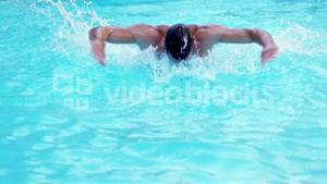 Handsome man swimming butterfly stroke