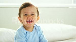 Cute baby with nightwear smiling and sitting on a bed