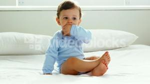 Cute baby with nightwear sitting on a bed