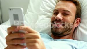 Man smiling and using smartphone on bed