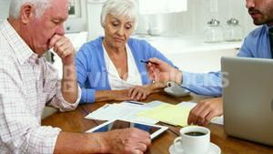 Mature couple filling some formal documents with man