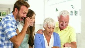 Happy family laughing in front of a tablet