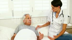 Nurse taking care of mature man lying on a bed