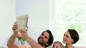 Cute family smiling and taking a photo with a tablet
