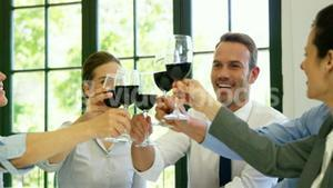 Business people are toasting with a red wine