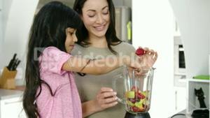 Happy mother and daughter making smoothies