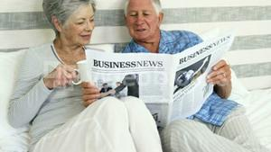 Happy senior couple reading a newspaper