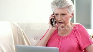 Old woman on a phone with her computer