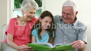 Girl reading a book with her grandparent