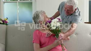 Old man surprising his wife with gifts